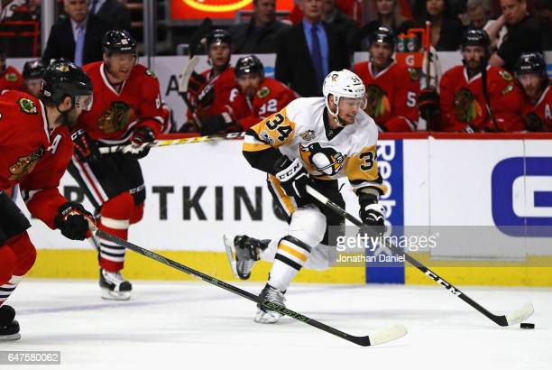 Tom Kuhnhackl of the Pittsburgh Penguins advances the puck in front of Marian Hossa and Brent Seabrook of the Chicago Blackhawks at the United Center...