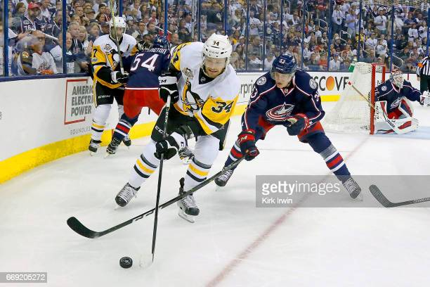 Tom Kuhnhackl of the Pittsburgh Penguins and Gabriel Carlsson of the Columbus Blue Jackets battle for control of the puck during the first period in...