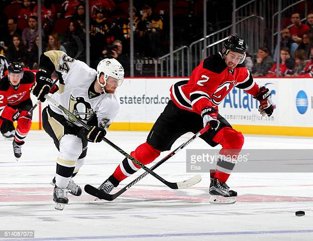 Tom Kuhnhackl of the Pittsburgh Penguins and John Moore of the New Jersey Devils chase after the puck in the third period on March 6 2016 at...