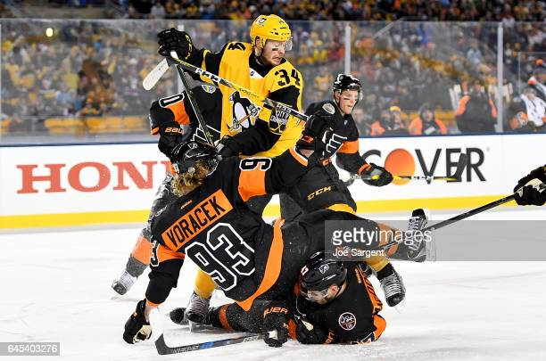 Tom Kuhnhackl of the Pittsburgh Penguins gets tied up with Jakub Voracek of the Philadelphia Flyers during the 2017 Coors Light NHL Stadium Series at...