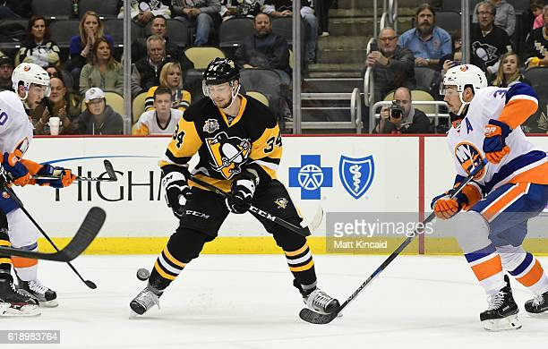 Tom Kuhnhackl of the Pittsburgh Penguins reaches for the puck against the New York Islanders at PPG PAINTS Arena on October 27 2016 in Pittsburgh...