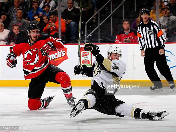 Tom Kuhnhackl of the Pittsburgh Penguins takes a shot as he collides with John Moore of the New Jersey Devils on March 6 2016 at Prudential Center in...