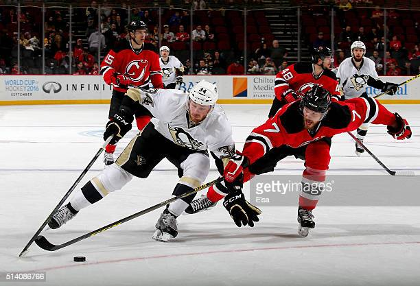 Tom Kuhnhackl of the Pittsburgh Penguins tries to keep the puck as Jon Merrill of the New Jersey Devils defends in the third period on March 6 2016...