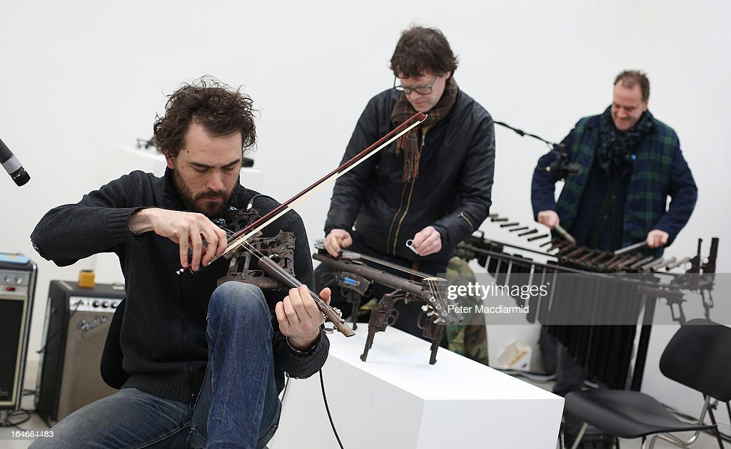 Tom Lamb, John Coxon and Charles Hayward perform on musical instruments made from recycled gun parts, at the Lisson Gallery on March 26, 2013 in London, England. Mexican artist Pedro Reyes received 6,700 destroyed weapons from the Mexican government from which he sculpted two groups of instruments. The first, a series titled Imagine, is an orchestra of fifty instruments, from flutes to string and percussion instruments, designed to be played live. The second, Disarm, is an installation of mechanical musical instruments, which can either be automated or played live by an individual operator using a laptop computer or midi keyboard.