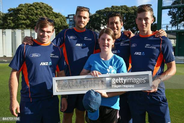 Tom Latham Tim Southee Mitchell Santner and Ross Taylor present a signed bat to thirteenyearold Erin Buckland who is 'flying the flag' for females in...