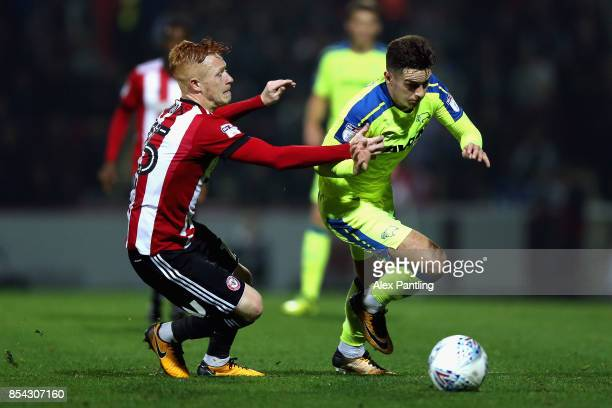 Tom Lawrence of Derby County is pulled back by Ryan Woods of Brentford during the Sky Bet Championship match between Brentford and Derby County at...