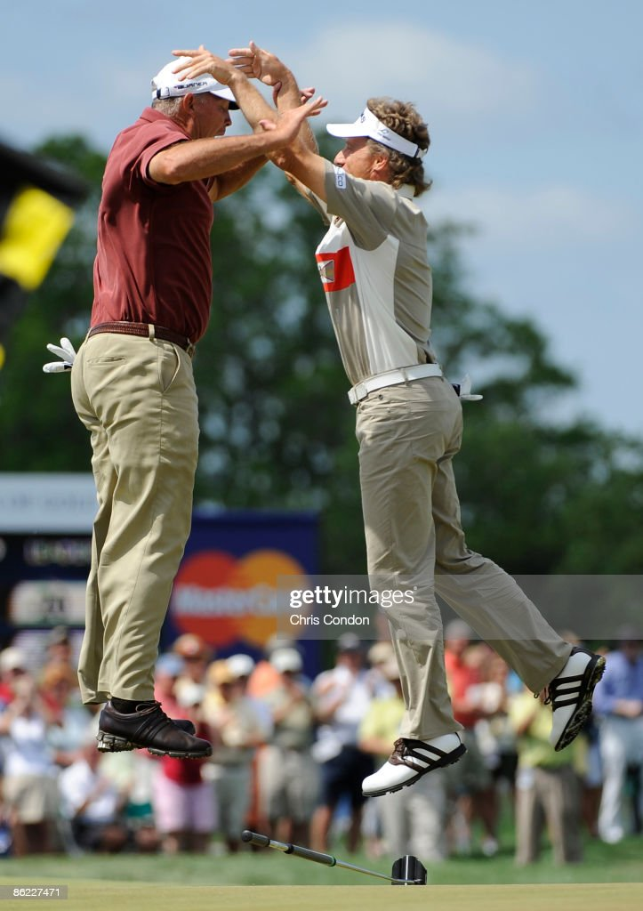 Tom Lehman and Bernhard Langer react after Langer sinks a birdie putt on the 18th green during the final round of the Legends Division at the Liberty...