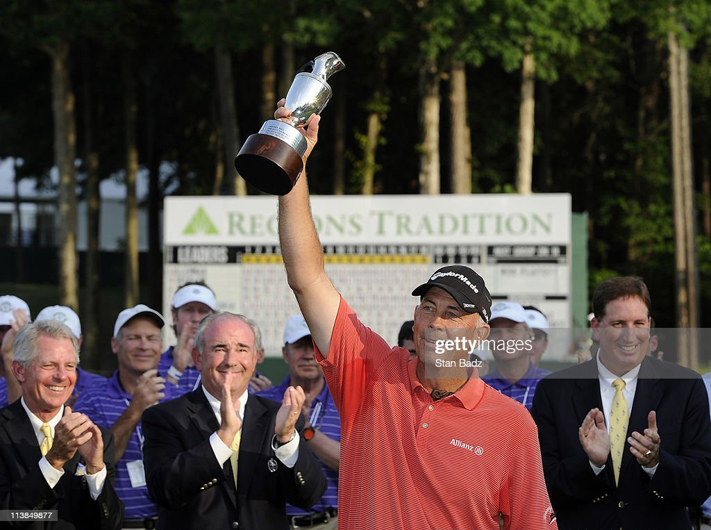 Tom Lehman holds the champion's trophy after winning in a two hole playoff against Peter Senior during the final round of the Regions Tradition at...