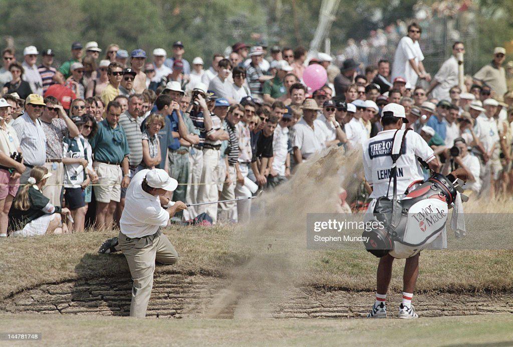 Tom Lehman of the United States chips out of the 3rd hole bunker as his caddy Andy Martinez looks on during the 125th Open Championship on 21st July...