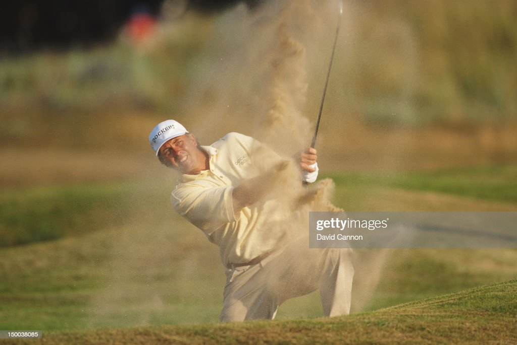 Tom Lehman of the United States hits out of the 18th hole bunker during his round of 64 at the 125th Open Championship on 20tht July 1996 at the...