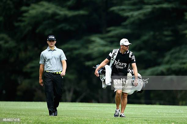 Tom Lewis of England walks down the first fairway with his caddie during the second round of the Joburg Open at Royal Johannesburg and Kensington...