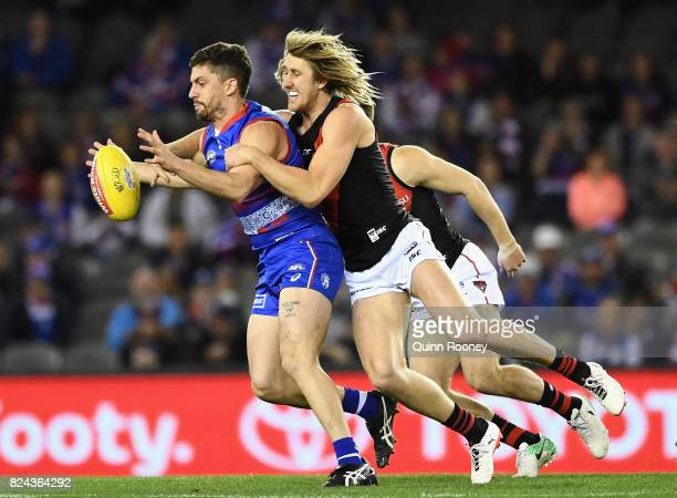 Tom Liberatore of the Bulldogs is tackled by Dyson Heppell of the Bombers during the round 19 AFL match between the Western Bulldogs and the Essendon...
