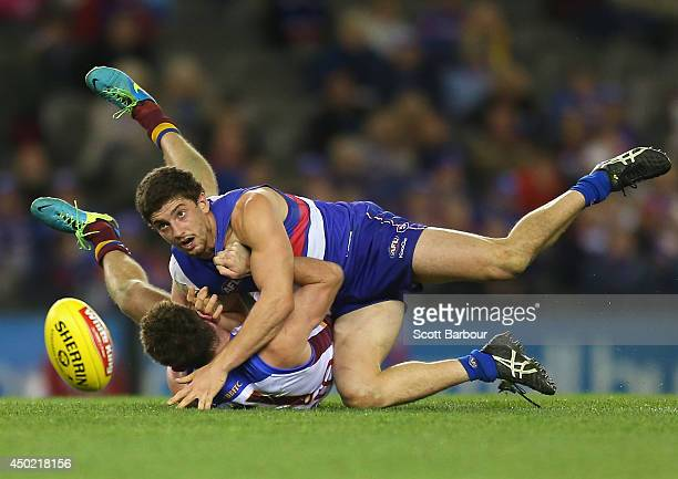 Tom Liberatore of the Bulldogs is tackled during the round 12 AFL match between the Western Bulldogs and the Brisbane Lions at Etihad Stadium on June...