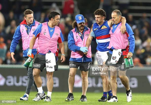 Tom Liberatore of the Bulldogs is taken from the ground after being concussed during the round six AFL match between the Greater Western Sydney...