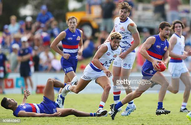 Tom Liberatore of the Bulldogs making his comeback from a knee reconstuction runs with the ball away from Jason Johannisen of the Bulldogs during the...