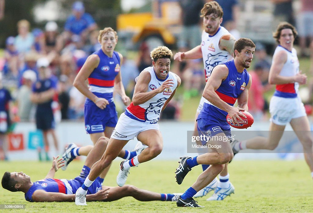 Tom Liberatore of the Bulldogs, making his comeback from a knee reconstuction, runs with the ball away from Jason Johannisen of the Bulldogs during the Western Bulldogs AFL intra-club match at Whitten Oval on February 13, 2016 in Melbourne, Australia.