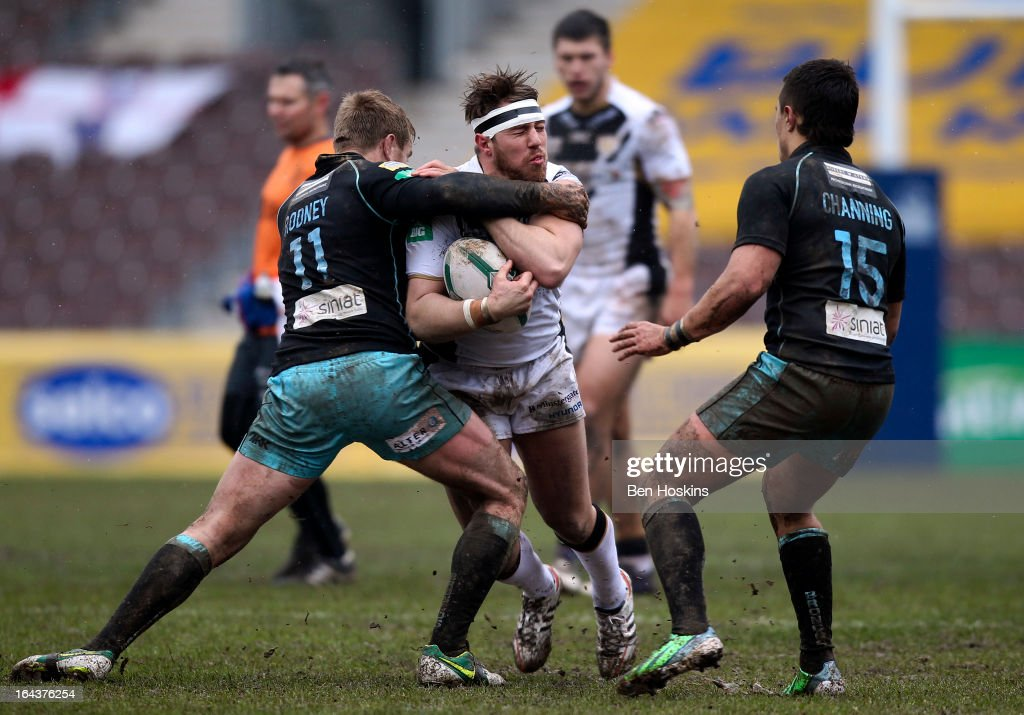 Tom Lineham of Hull is tackled by Shane Rodney (L) of the London Broncos during the Super League match between London Broncos and Hull at Twickenham Stoop on March 23, 2013 in London, England.