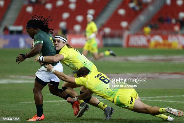 Tom Lucas and John Porch of Australia tackle Branco Du Preez of South Africa during the Cup Quarter Finals 2017 Singapore Sevens match between...