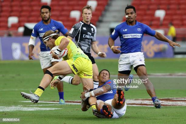 Tom Lucas of Australia is tackled during the 2017 Singapore Sevens match between Australia and Samoa at National Stadium on April 15 2017 in Singapore