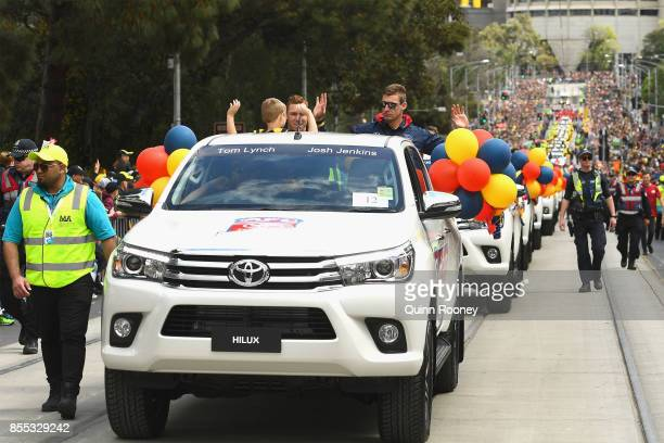 Tom Lynch and Josh Jenkins of the Crows wave to the crowd during the 2017 AFL Grand Final Parade ahead of the Grand Final between the Adelaide Crows...