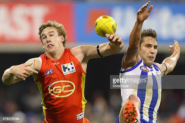 Tom Lynch of the Suns and Jamie Macmillan of the Kangaroos compete for the ball during the round 14 AFL match between the Gold Coast Suns and the...