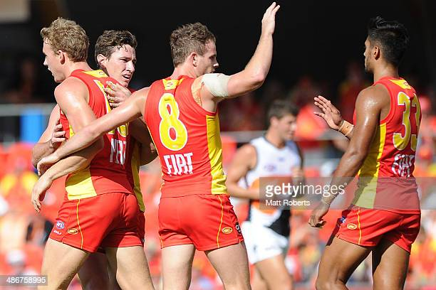 Tom Lynch of the Suns celebrates kicking a goal with teammates during the round six AFL match between the Gold Coast Suns and the Greater Western...