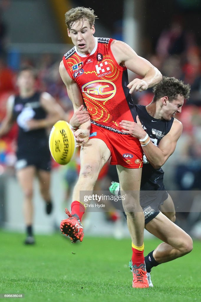 Tom Lynch of the Suns is tackled by Kade Simpson of the Blues during the round 13 AFL match between the Gold Coast Suns and the Carlton Blues at Metricon Stadium on June 17, 2017 in Gold Coast, Australia.