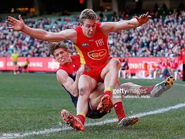 Tom Lynch of the Suns is tackled by Sam Frost of the Demons during the 2016 AFL Round 19 match between the Melbourne Demons and the Gold Coast Suns...