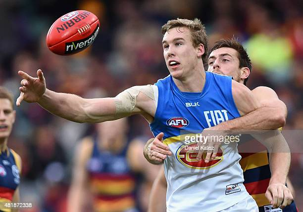 Tom Lynch of the Suns looks to control the ball as he is tackled by Richard Douglas of the Crows during the round 17 AFL match between the Adelaide...