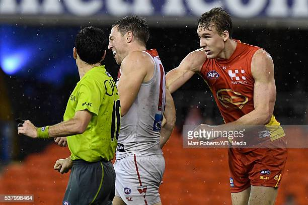Tom Lynch of the Suns punches Jeremy Laidler of the Swans during the round 11 AFL match between the Gold Coast Suns and the Sydney Swans at Metricon...