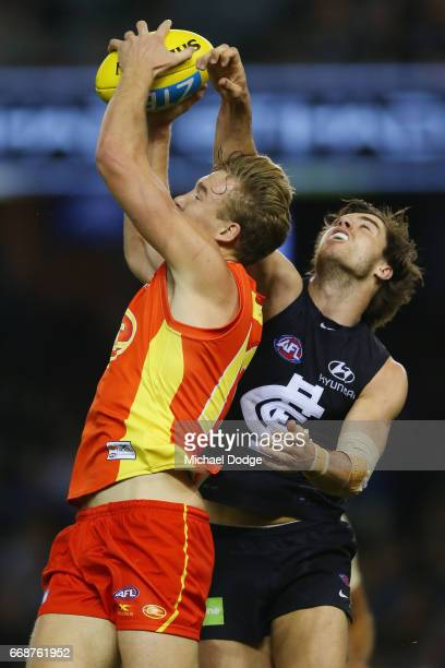 Tom Lynch of the Sunsmarks the ball against Lachie Plowman of the Blues during the round four AFL match between the Carlton Blues and the Gold Coast...