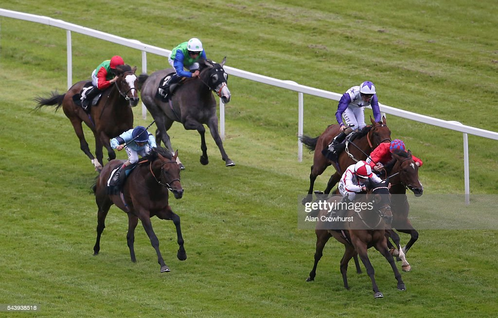 Tom Marquand riding Scarlet Dragon (R, white) win The Pelican Handicap Stakes at Newbury racecourse on June 30, 2016 in Newbury, England.