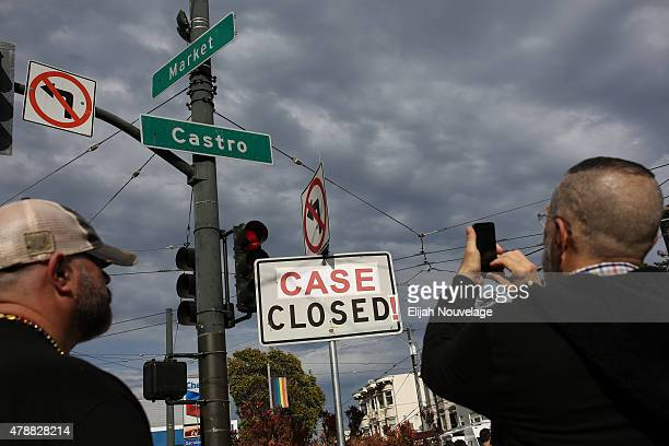 Tom Marsella R takes a photo of a street sign modified to say 'CASE CLOSED' as Mitchell Horowitz his husband of seven years looks on during a gay...