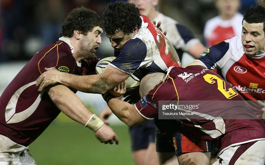Tom Marshall of Tasman tries to break the tackle of Jamie Mackintosh and Jason Rutledge during the round five ITM Cup match between Tasman and...