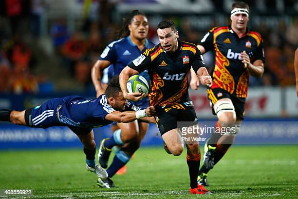 Tom Marshall of the Chiefs breaks the tackle of Jamison GibsonPark of the Blues during the round eight Super Rugby match between the Chiefs and the...