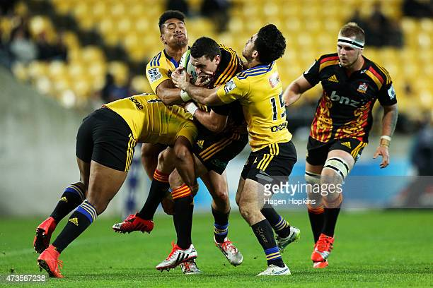 Tom Marshall of the Chiefs is tackled by Julian Savea Ardie Savea and Nehe MilnerSkudder of the Hurricanes during the round 14 Super Rugby match...