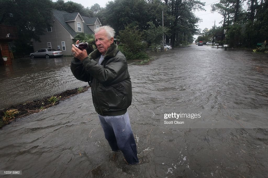 Tom Marshall takes a picture of his flooded home as he stands in floodwater resulting from Hurricane Irene on August 27, 2011 in Kill Devil Hills, North Carolina. Hurricane Irene hit Dare County, which sits along the Outer Banks and includes the vacation towns of Nags Head, Kitty Hawk and Kill Devil Hills, as a category one hurricane around mid-day today causing wind damage and flooding.