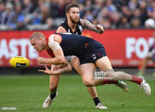 Tom McDonald of the Demons handballs whilst being tackled by Jeremy Howe of the Magpies during the round 12 AFL match between the Melbourne Demons...