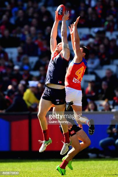 Tom McDonald of the Demons marks infront of Jake Barrett of the Lions during the round 22 AFL match between the Melbourne Demons and the Brisbane...