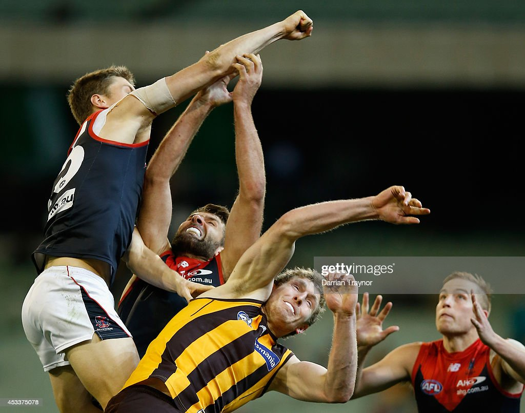 Tom McDonald of the Demons punches the ball clear of Ben McEvoy of the Hawks during the round 20 AFL match between the Hawthorn Hawks and the Melbourne Demons at Melbourne Cricket Ground on August 9, 2014 in Melbourne, Australia.