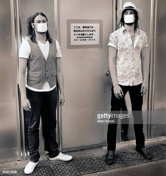 Tom Meighan and Sergio Pizzorno of Kasabian pose for a portrait wearing swine flu protection masks in Japan in May 2009
