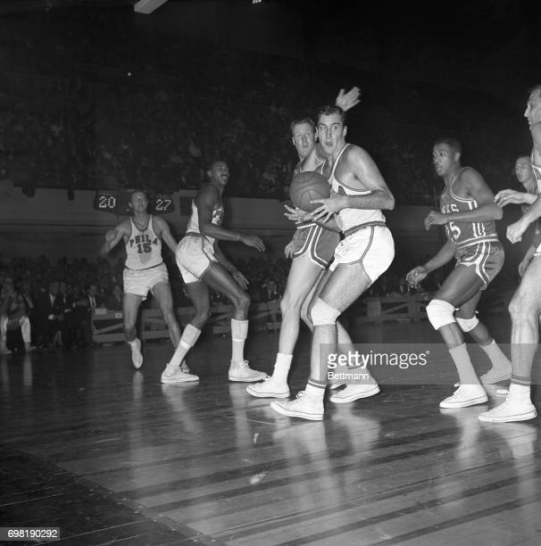 Tom Meschery of the Warriors looks for somebody to pass off to as he's harassed by Clyde Lovellette of St Louis' Hawks during 1st quarter here 12/6