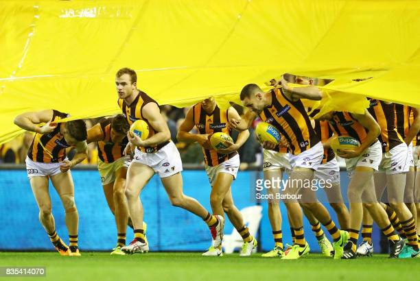 Tom Mitchell of the Hawks and his teammates run through the banner during the round 22 AFL match between the Carlton Blues and the Hawthorn Hawks at...