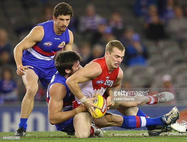 Tom Mitchell of the Swans is tackled by Tom Campbell of the Bulldogs during the round 22 AFL match between the Western Bulldogs and the Sydney Swans...