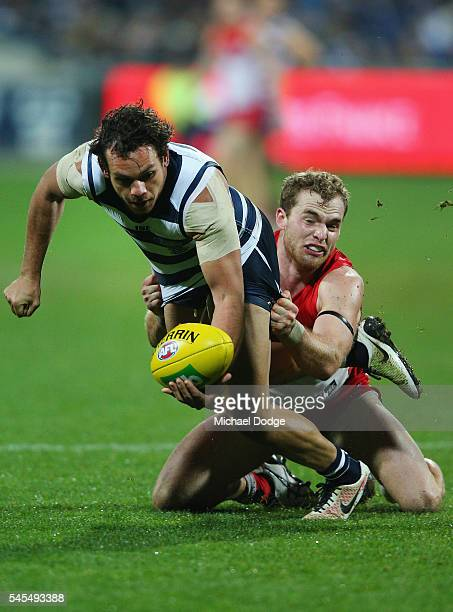 Tom Mitchell of the Swans tackles Steven Motlop of the Cats during the round 16 AFL match between the Geelong Cats and the Sydney Swans at Simonds...