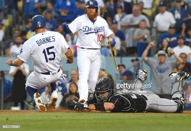 Tom Murphy of the Colorado Rockies misses the tag on Austin Barnes of the Los Angeles Dodgers as he is safe at home in the second inning of the game...