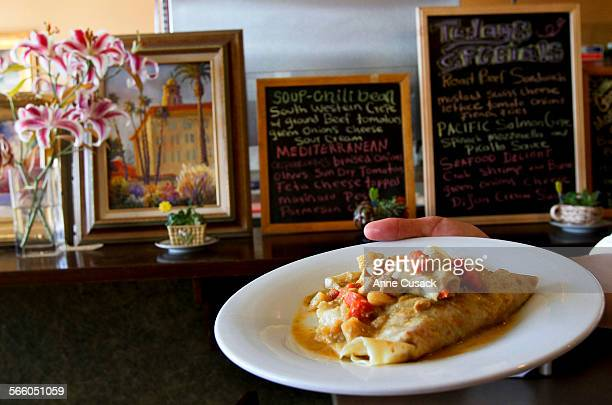 Tom Muvihill holds one of his dinner crepes made with chicken and a Thai yellow curry in his Delightful Crepes Cafe in Long Beach for business...