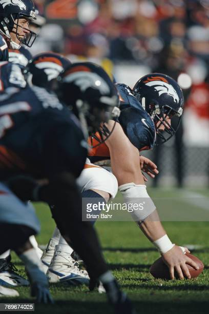 Tom Nalen Center for the Denver Broncos prepares to snap the ball as Quarterback John Elway calls the play during the American Football Conference...