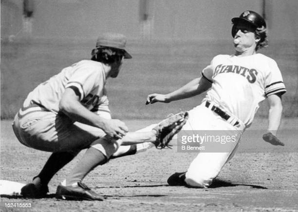 Tom O'Malley of the San Francisco Giants blows a bubble as he slides safely into thrid as Duane Walker of the Cincinnati Reds tries to make the tag...