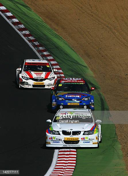 Tom Onslow Cole of Great Britain drives the ebay Motors BMW 320si ahead of Jason Plato driving the MG KX Momentum Racing MG6 and Gordon Shedden in...